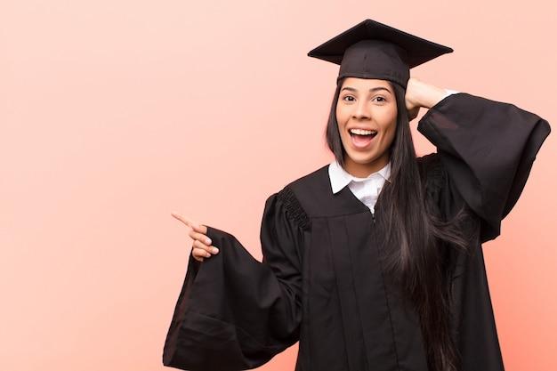 Junge lateinamerikanische studentin lacht, sieht glücklich, positiv und überrascht aus und verwirklicht eine großartige idee, die auf seitlichen kopierraum zeigt