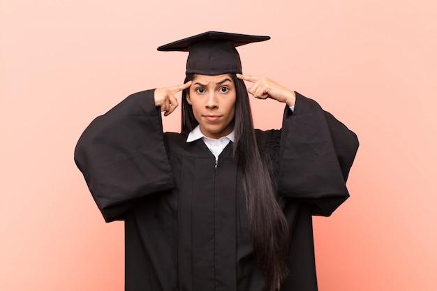 Junge lateinamerikanische studentin mit einem ernsten und konzentrierten blick, brainstorming und nachdenken über ein herausforderndes problem
