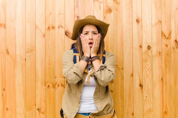 Junge lateinische forscherfrau gegen hölzerne wand