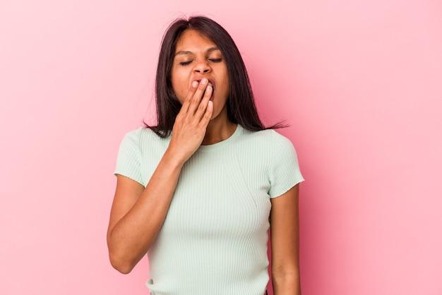 Junge lateinische frau, die auf rosafarbenem hintergrund isoliert gähnt und eine müde geste zeigt, die den mund mit der hand bedeckt.