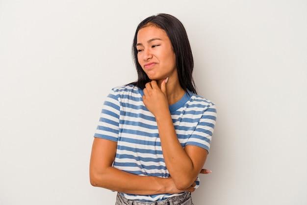 Junge lateinische frau, die auf weißem hintergrund isoliert ist, leidet an halsschmerzen aufgrund eines virus oder einer infektion.