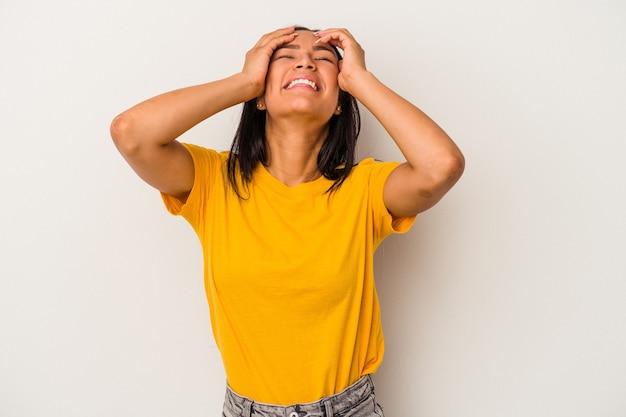 Junge lateinische frau, die auf weißem hintergrund lokalisiert wird, lacht freudig die hände auf dem kopf. glück-konzept.