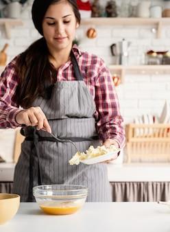 Junge lateinische frau, die butter beim kochen an der küche hinzufügt