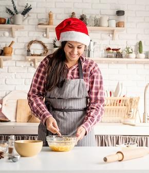 Junge lateinische frau, die eier kocht, die an der küche kochen