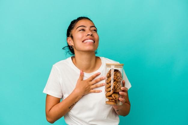 Junge lateinische frau, die ein keksglas isoliert auf blauem hintergrund hält, lacht laut und hält die hand auf der brust.