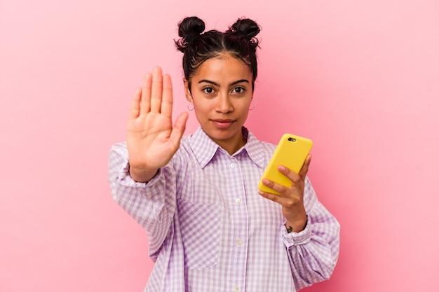 Junge lateinische frau, die ein mobiltelefon einzeln auf rosafarbenem hintergrund hält, das mit ausgestreckter hand steht und ein stoppschild zeigt und sie verhindert.