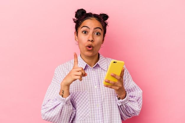 Junge lateinische frau, die ein mobiltelefon einzeln auf rosafarbenem hintergrund hält und eine großartige idee hat, konzept der kreativität.