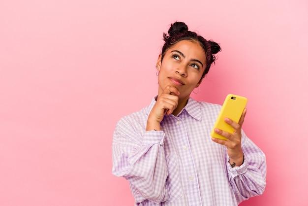 Junge lateinische frau, die ein mobiltelefon einzeln auf rosafarbenem hintergrund hält und seitlich mit zweifelhaftem und skeptischem ausdruck schaut.