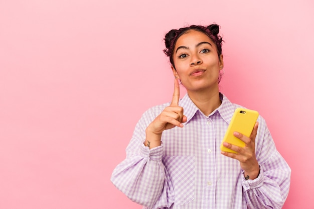Junge lateinische frau, die ein mobiltelefon hält, das auf rosafarbenem hintergrund isoliert ist und die nummer eins mit dem finger zeigt.