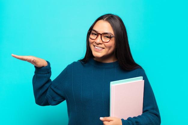 Junge lateinische frau, die ein objekt mit beiden händen auf seitenkopierraum hält, ein objekt zeigend, anbietet oder bewirbt