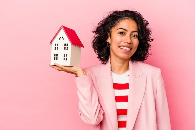 Junge lateinische frau, die ein spielzeughaus isoliert auf rosa hintergrund hält, das einen kopienraum auf einer handfläche zeigt und eine andere hand an der taille hält.