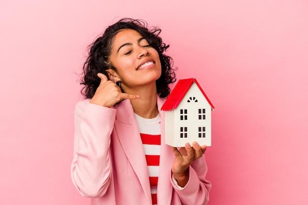 Junge lateinische frau, die ein spielzeughaus lokalisiert auf rosa hintergrund hält, der eine handy-anrufgeste mit den fingern zeigt.