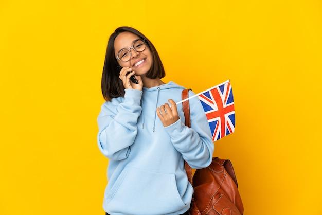 Junge lateinische frau, die eine britische flagge lokalisiert auf gelbem hintergrund hält, die ein gespräch mit dem mobiltelefon hält