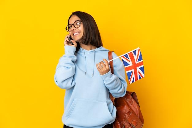 Junge lateinische frau, die eine britische flagge lokalisiert auf gelbem hintergrund hält, die ein gespräch mit dem mobiltelefon mit jemandem hält