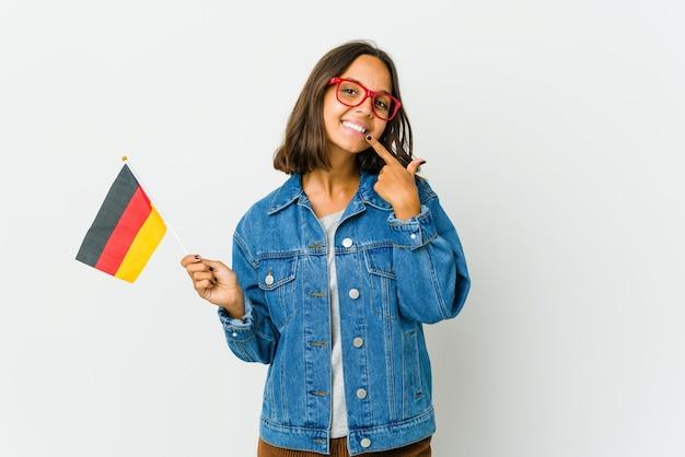 Junge lateinische frau, die eine deutsche fahne lokalisiert auf weißem wandlächeln hält und finger auf mund zeigt.