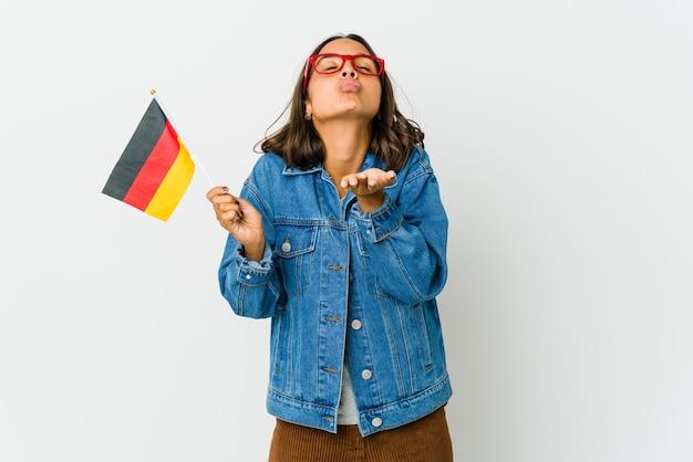 Junge lateinische frau, die eine deutsche fahne lokalisiert auf weißen wandfaltenlippen hält und palmen hält, um luftkuss zu senden.