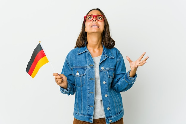 Junge lateinische frau, die eine deutsche fahne lokalisiert auf weißer wand hält, die zum himmel schreit und aufschaut, frustriert.