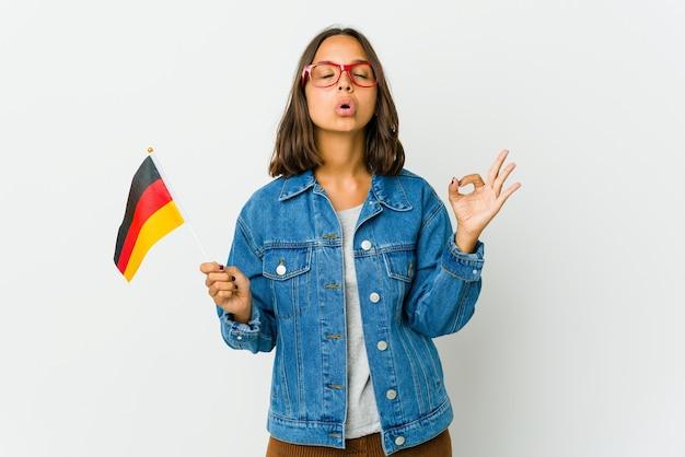 Junge lateinische frau, die eine deutsche fahne lokalisiert auf weißer wand hält, entspannt sich nach hartem arbeitstag, sie führt yoga durch.