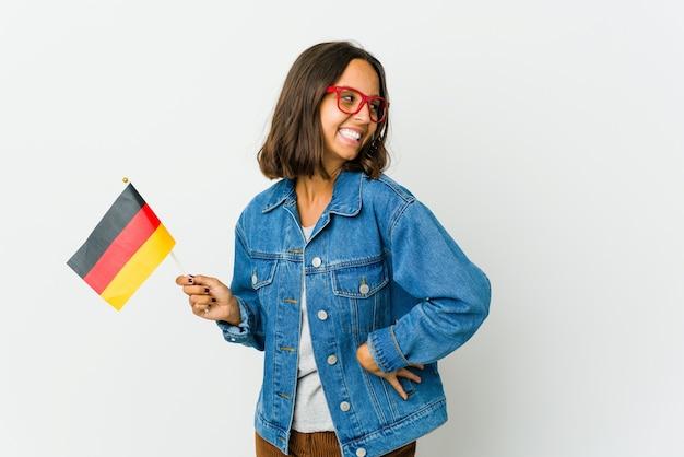 Junge lateinische frau, die eine deutsche flagge lokalisiert auf weißem hintergrund hält, lacht und schließt augen, fühlt sich entspannt und glücklich.
