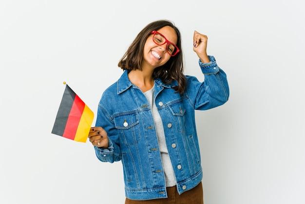 Junge lateinische frau, die eine deutsche flagge lokalisiert auf weißer wand hält, die einen sieg, leidenschaft und begeisterung, glücklichen ausdruck feiert.