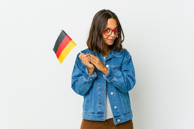 Junge lateinische frau, die eine deutsche flagge lokalisiert auf weißer wand hält, die plan im sinn bildet, eine idee aufstellend.
