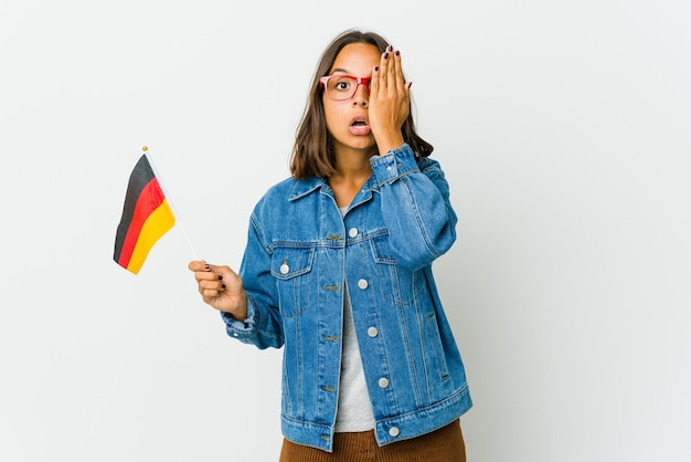 Junge lateinische frau, die eine deutsche flagge lokalisiert auf weißer wand hält, die spaß hat, die hälfte des gesichts mit handfläche bedeckt.