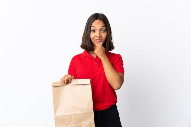 Junge lateinische frau, die eine einkaufstasche des lebensmittels hält
