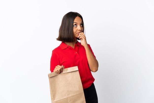 Junge lateinische frau, die eine einkaufstasche des lebensmittels lokalisiert auf weiß hält, das zweifel beim nachschlagen hat