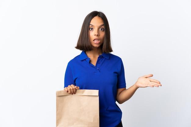 Junge lateinische frau, die eine einkaufstasche des lebensmittels lokalisiert auf weiß hält, das zweifel geste macht