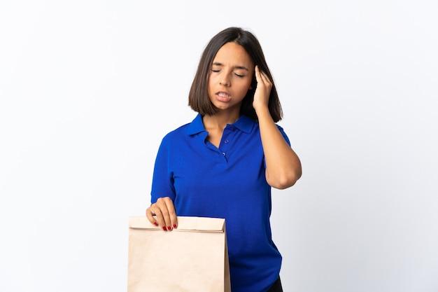 Junge lateinische frau, die eine einkaufstasche des lebensmittels lokalisiert auf weiß mit kopfschmerzen hält