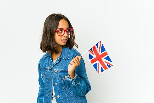 Junge lateinische frau, die eine englische flagge lokalisiert auf weißer wand hält, schaut beiseite lächelnd, fröhlich und angenehm.