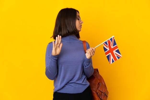 Junge lateinische frau, die eine flagge des vereinigten königreichs auf gelbem hintergrund isoliert hält und eine stopp-geste macht und enttäuscht