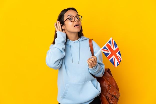 Junge lateinische frau, die eine flagge des vereinigten königreichs hält, die auf gelbem hintergrund isoliert ist und etwas hört, indem sie die hand auf das ohr legt