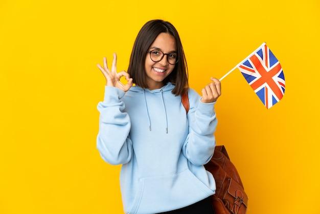 Junge lateinische frau, die eine flagge des vereinigten königreichs hält, die auf gelber oberfläche isoliert ist und ein ok-zeichen mit den fingern zeigt