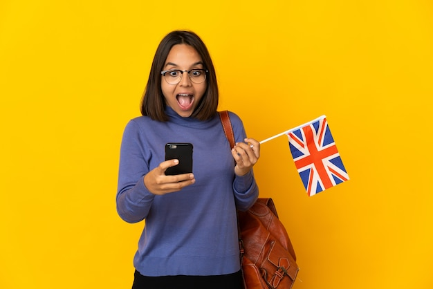 Junge lateinische frau, die eine flagge des vereinigten königreichs lokalisiert auf gelbem hintergrund hält, überrascht und eine nachricht sendend