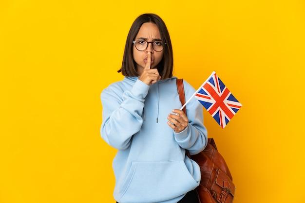 Junge lateinische frau, die eine flagge großbritanniens isoliert hält