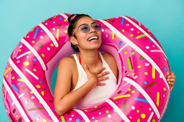 Junge lateinische frau, die einen aufblasbaren donut auf blauem hintergrund hält, lacht laut und hält die hand auf der brust.
