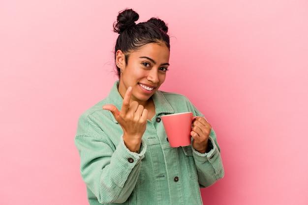 Junge lateinische frau, die einen becher einzeln auf rosafarbenem hintergrund hält und mit dem finger auf sie zeigt, als ob sie einladen würde, näher zu kommen.