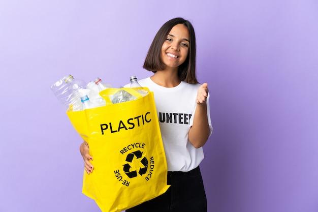 Junge lateinische frau, die einen recyclingbeutel voll papier hält, um isoliert auf lila händeschütteln für das schließen eines guten geschäfts zu recyceln
