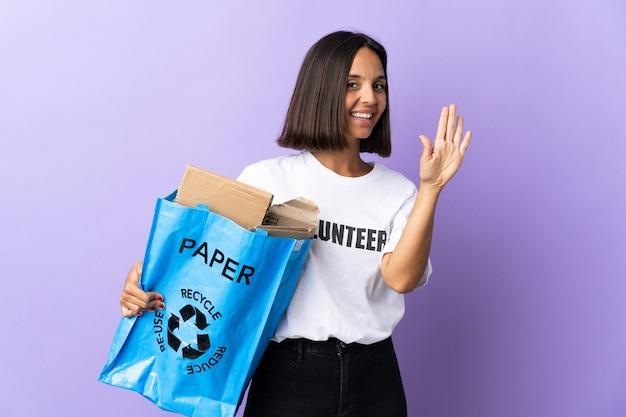 Junge lateinische frau, die einen recyclingbeutel voll papier hält, um lokalisiert auf lila salutieren mit hand mit glücklichem ausdruck zu recyceln