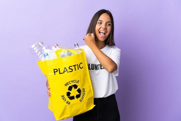 Junge lateinische frau, die einen recyclingbeutel voll papier hält, um zu recyceln