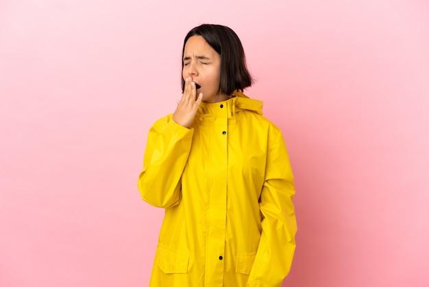 Junge lateinische frau, die einen regendichten mantel über einer isolierten wand trägt, gähnt und den weit geöffneten mund mit der hand bedeckt
