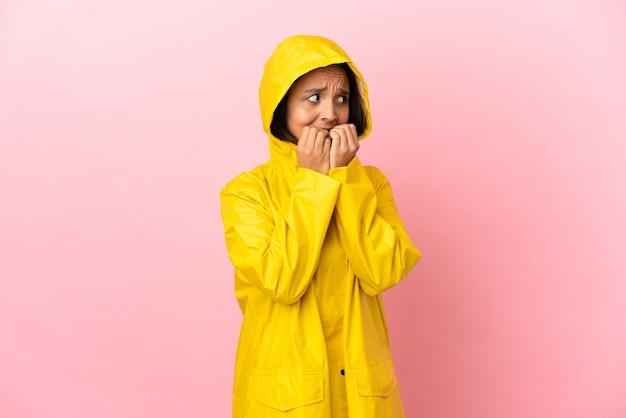 Junge lateinische frau, die einen regendichten mantel über isoliertem hintergrund trägt, nervös und verängstigt, die hände zum mund