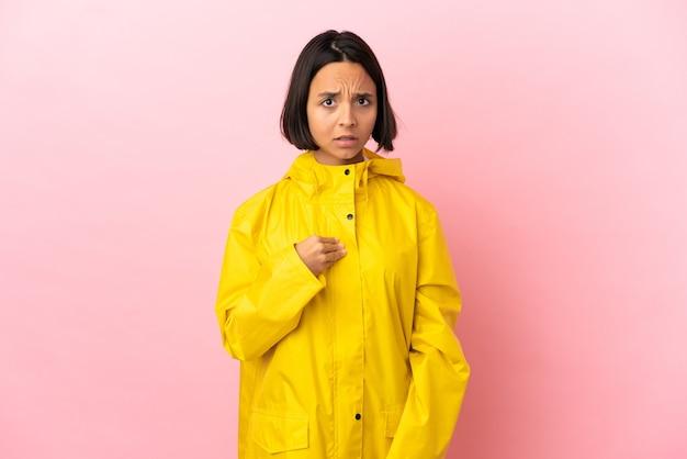 Junge lateinische frau, die einen regendichten mantel über isoliertem hintergrund trägt und auf sich selbst zeigt