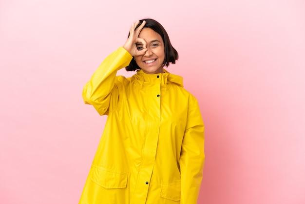 Junge lateinische frau, die einen regendichten mantel über isoliertem hintergrund trägt und ein okay-zeichen mit den fingern zeigt