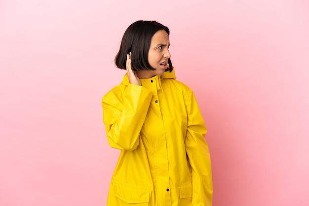 Junge lateinische frau, die einen regendichten mantel über isoliertem hintergrund trägt und etwas hört, indem sie die hand auf das ohr legt