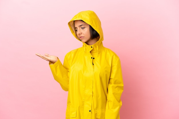 Junge lateinische frau, die einen regendichten mantel über isoliertem hintergrund trägt und kopienraum mit zweifeln hält
