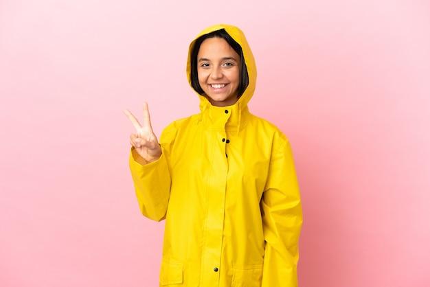 Junge lateinische frau, die einen regendichten mantel über isoliertem hintergrund trägt und lächelt und zeigt victory-zeichen