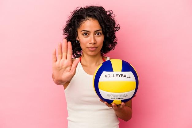 Junge lateinische frau, die einen volleyballball lokalisiert auf rosa hintergrund hält, der mit ausgestreckter hand steht