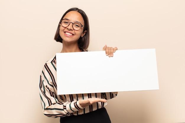Junge lateinische frau, die fröhlich lächelt, sich glücklich fühlt und ein konzept im kopierraum mit handfläche zeigt